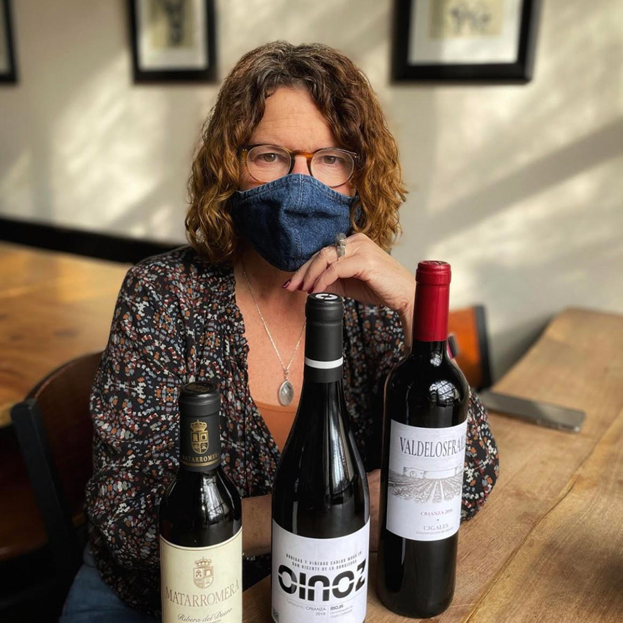 Jan Bugher sitting with three bottles of wine
